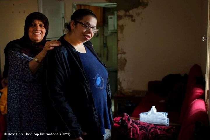 A Syrian woman living in Lebanon is standing in front of a camera together with her granddaughter who has an intellectual impairment.